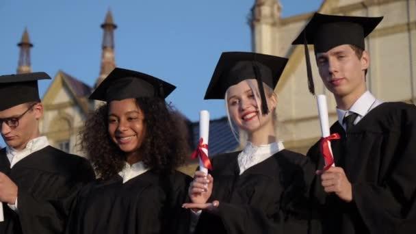 Absolventi pózují před kamerou a ukazují své diplomy.
