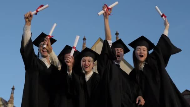 Finally free. Group of cheerful students wearing graduation gowns and masters caps standing together holding their diplomas after graduation.