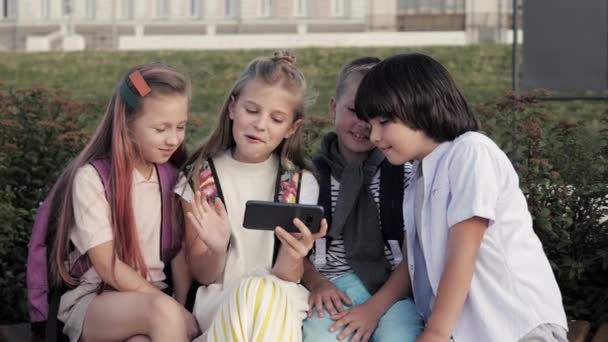 Emotional kids watching something on the phone outdoors and talking.