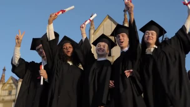 Happy group of students with arms up at their graduation.