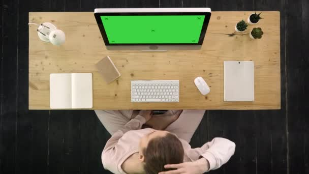 Woman stretching her tense nape in the office in front of the computer monitor. Green Screen Mock-up Display.