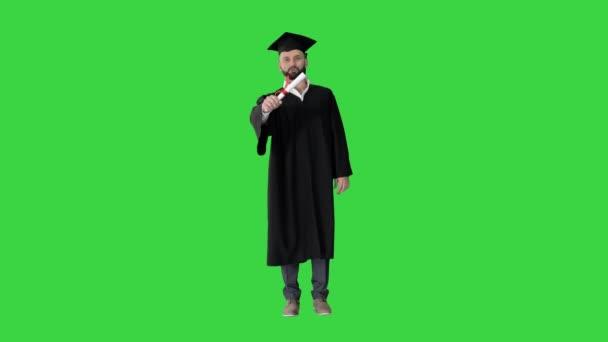 Šťastný mladý muž v maturitní čepici držící diplom a mluvící na zelené obrazovce, Chroma Key.