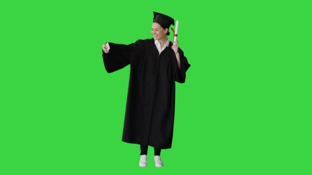 Happy female graduate holding diploma and making selfie on her phone on a Green Screen, Chroma Key.