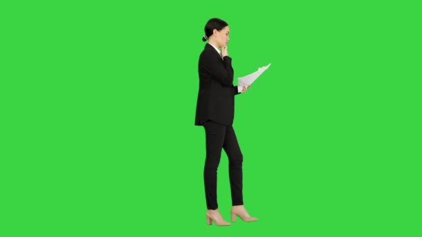 Serious Businesswoman reading report preparing for a presentation while walking on a Green Screen, Chroma Key.