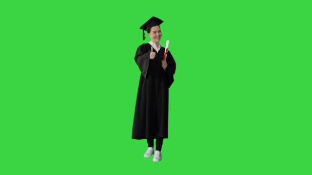 Šťastný absolvent žena drží diplom a palec nahoru na zelené obrazovce, Chroma Key.