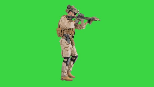 Soldier Walking and Aims through the Assault Rifle on a Green Screen, Chroma Key.