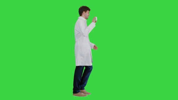 Smiling male doctor with stethoscope walking and advertising pills on a Green Screen, Chroma Key.