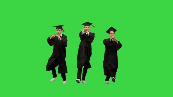 Three male graduates in robes and mortarboards dancing in synch on a Green Screen, Chroma Key.