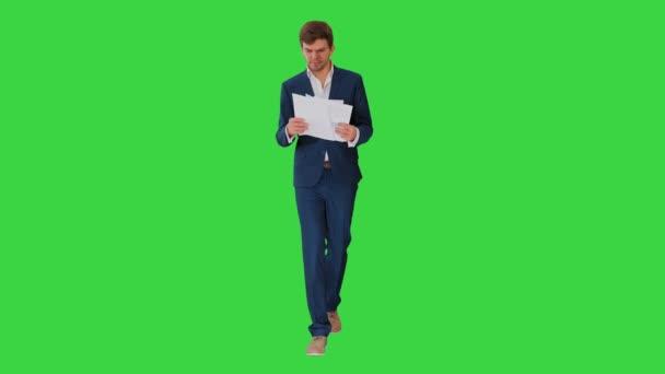 Komoly üzletember dokumentumok olvasása vagy jelentés séta közben a zöld képernyőn, Chroma Key.