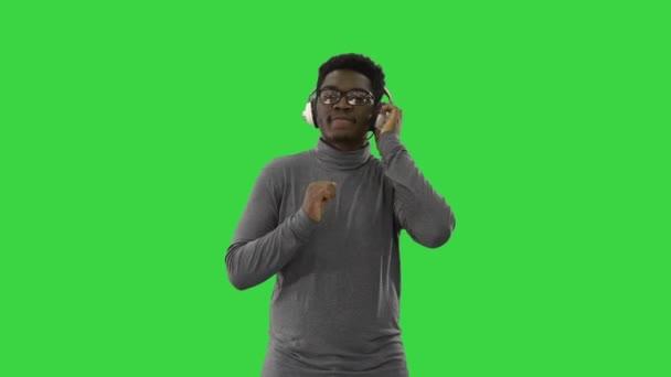 Usmívající se africký Američan ve sluchátkách a pohybující se do rytmu hudby na zelené obrazovce, Chroma Key.