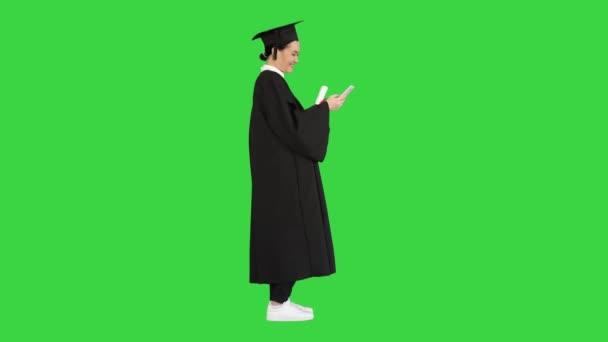 Boldog női diplomás kezében diploma és sms-ezés a telefonján egy zöld képernyőn, Chroma Key.