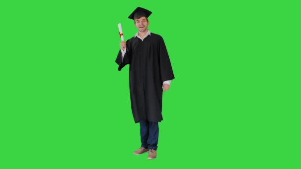 Happy male student in graduation robe posing and waiving with his diploma on a Green Screen, Chroma Key.