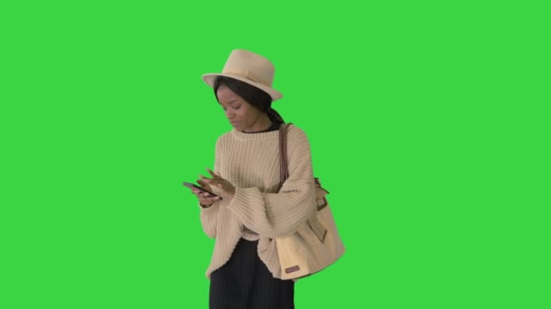 Stylish african american woman in knitwear and hat using her phone while walking on a Green Screen, Chroma Key.