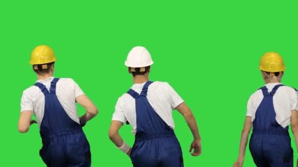 Tři dělníci v tvrdých kloboucích tančí zády ke kameře na zelené obrazovce, Chroma Key.