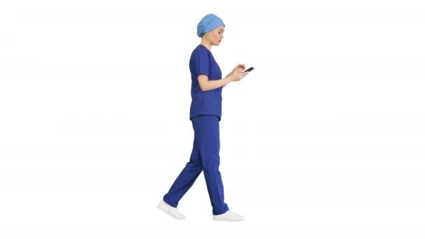 Női orvos vagy nővér kék egyenruhában használja a telefont, miközben sétál, Alpha Channel