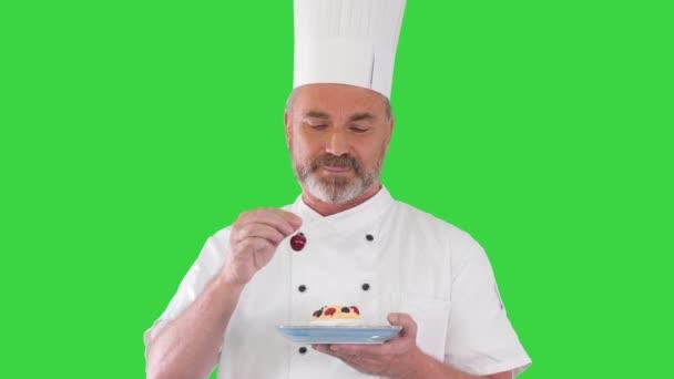 Šéf dát třešeň na dortu před podáváním to Icing na dortu na zelené obrazovce, Chroma Key.