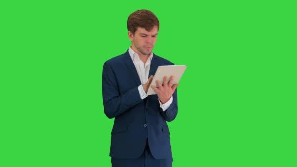 Magabiztos vállalkozó öltözött öltöny dolgozik digitális tabletta egy zöld képernyőn, Chroma Key.