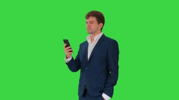 Komoly üzletember nézi a telefonját egy zöld képernyőn, Chroma Key.