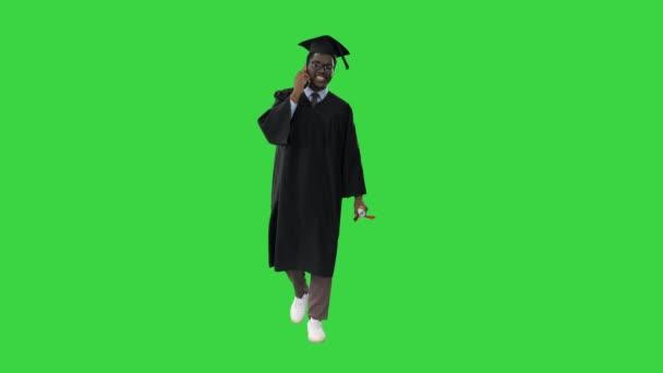 Mosolygó afro-amerikai férfi diák ballagási köntösben beszél telefonon, miközben sétál a zöld képernyőn, Chroma Key.