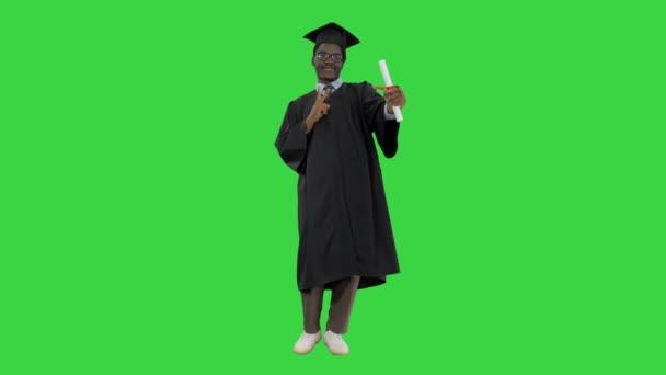 Boldog afro-amerikai férfi diák ballagási köntösben pózol diplomával a kamera egy zöld képernyőn, Chroma Key.