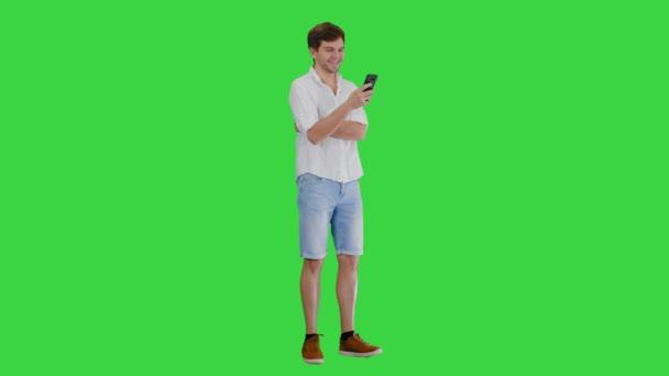 Jóképű fiatalember használja az okostelefonját, és nevet a zöld képernyőn, Chroma Key.