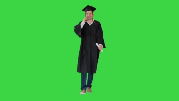 Muž absolvent v županu a minometu mluví do telefonu, zatímco chodí se svým diplomem na zelené obrazovce, Chroma Key.