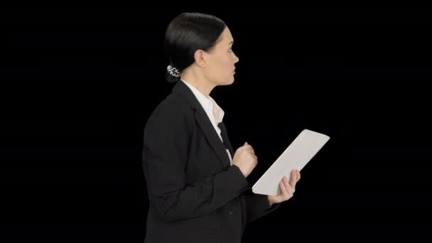 Üzletasszony használ tabletta pad gyaloglás közben, Alpha Channel