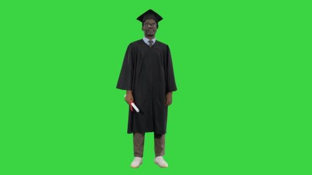Afričtí američtí studenti v maturitním županu skládací paže s diplomem dívá s velkým úsměvem na kameru na zelené obrazovce, Chroma Key.