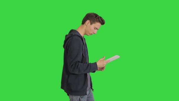 Fiatal férfi digitális táblagép használata közben séta a zöld képernyőn, Chroma Key.