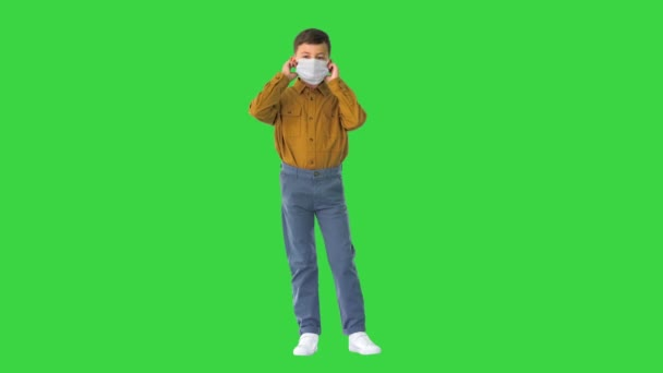 Little boy taking his face mask off and smiling at camera on a Green Screen, Chroma Key.