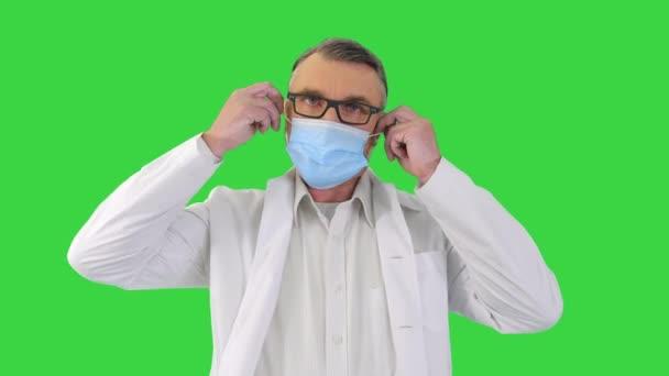 Férfi orvos leveszi védő orvosi maszk és mosolygós kamera egy zöld képernyőn, Chroma Key.