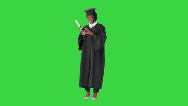 Boldog afro-amerikai női diplomás kezében diploma és SMS-t a telefonján egy zöld képernyőn, Chroma Key.