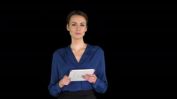 Egy hölgy rövid hajjal, formális ruhában, tablettával a kezében, és a kamerába beszél, Alpha Channel.