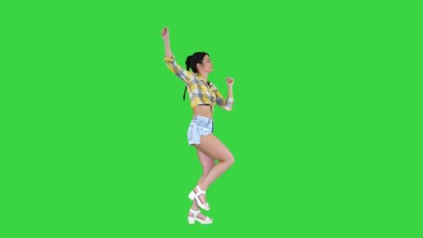 Herrliche süße Mädchen in Jeans Shorts, Turnschuhen, tanzen auf einem Green Screen, Chroma Key.