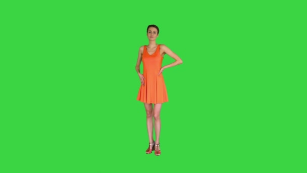 A beautiful, cheerful woman straightens her dress on a Green Screen, Chroma Key.