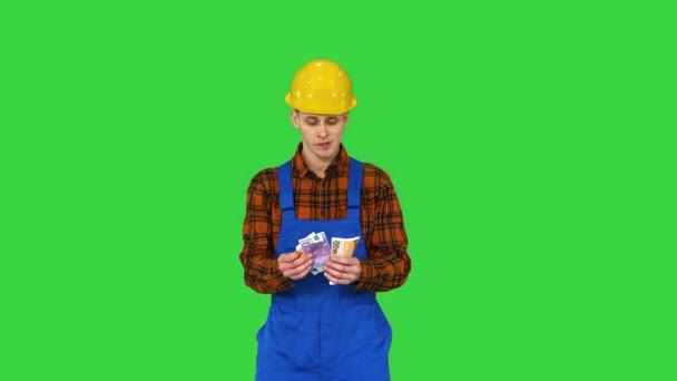 A workman counting cash in exaggerated way and dancing after that on a Green Screen, Chroma Key.
