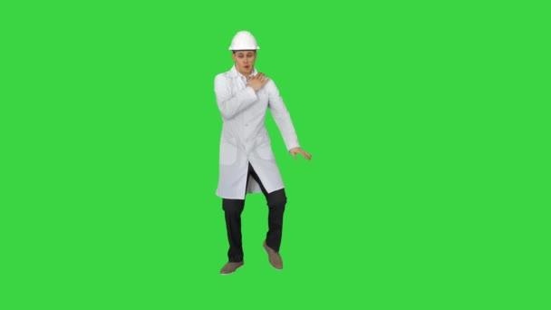 Vicces tudós fehér köntösben és biztonsági sisak táncol a zöld képernyőn, Chroma Key.