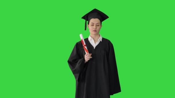 Frusztrált női diák ballagási köntösben rázza a diplomáját, miközben várja a zöld vásznat, Chroma Key.