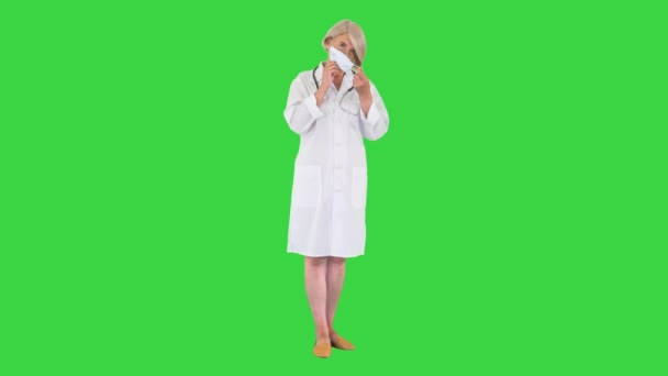 Senior woman doctor putting on medical mask looking at the camera on a Green Screen, Chroma Key.