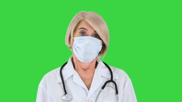Idősebb orvos vagy nővér leveszi orvosi maszk mosolyogva a zöld képernyőn, Chroma Key.