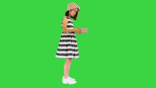 Ázsiai lány kinyitja a dobozt ajándékkal egy zöld képernyőn, Chroma Key.
