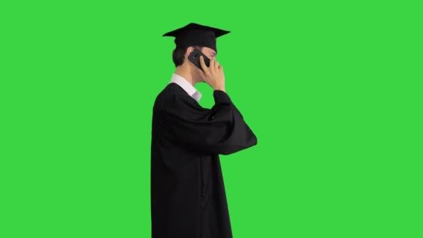 Az érettségiző diák elkezd sétálni és telefonál egy zöld képernyőn, Chroma Key.