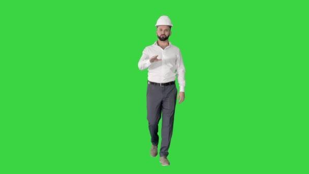 Mérnök keménykalapban séta és magyarázó valamit a zöld képernyőn, Chroma Key.