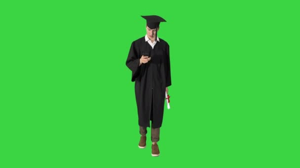 Smiling student walking and texting on his phone on a Green Screen, Chroma Key.