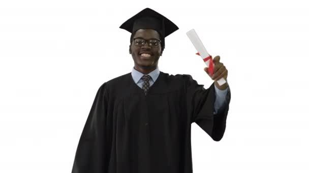 Šťastný africký americký muž student v maturitní župan chůze s diplomem a mluvit s kamerou na bílém pozadí.