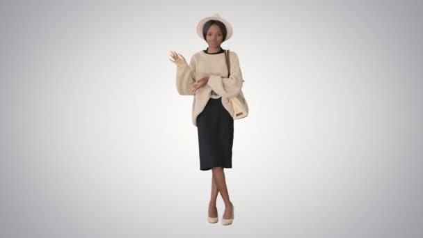 Mladý africký americký žena v pletený a bílý klobouk mluvení a gestikulace na gradient pozadí.