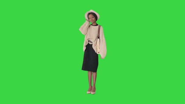 Fashionable african american woman posing in knitwear and white hat on a Green Screen, Chroma Key.