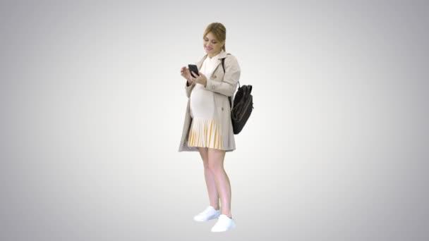 Terhes alkalmi nő kezében mobiltelefon sms-t gradiens háttér.