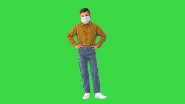 Boy wearing protective face mask looking at camera on a Green Screen, Chroma Key.