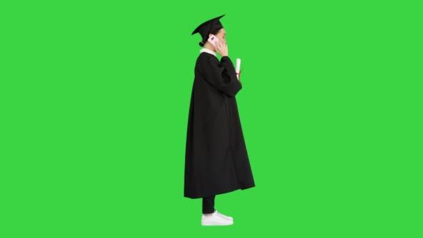 Érzelmi női hallgató ballagási köntösben beszél a telefonon kezében diploma egy zöld képernyőn, Chroma Key.
